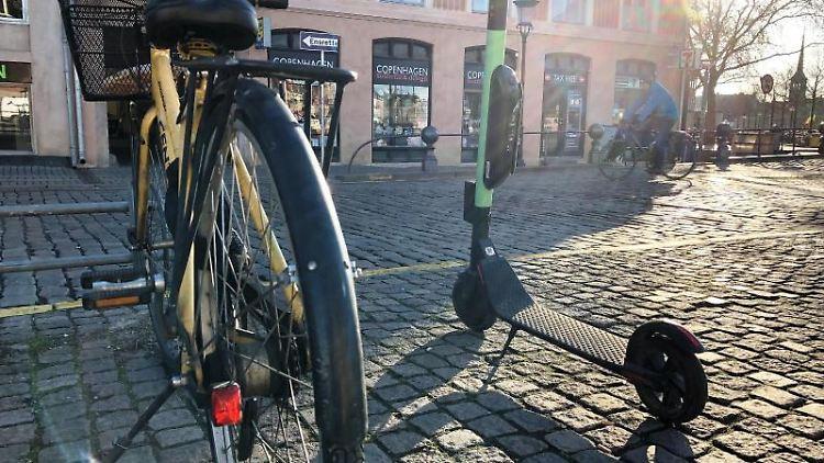 Ein Fahrrad steht in einer Innenstadt neben einem E-Tretroller. Foto: Steffen Trumpf/Archivbild