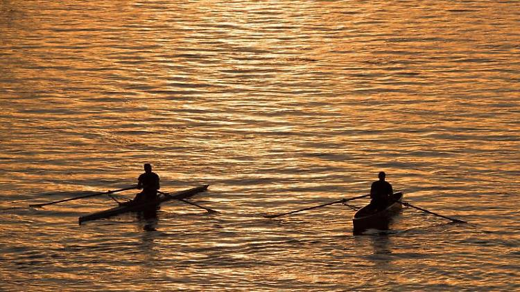 Zwei Ruderer sind bei Sonnenuntergang unterwegs. Foto: Sebastian Kahnert/Archivbild