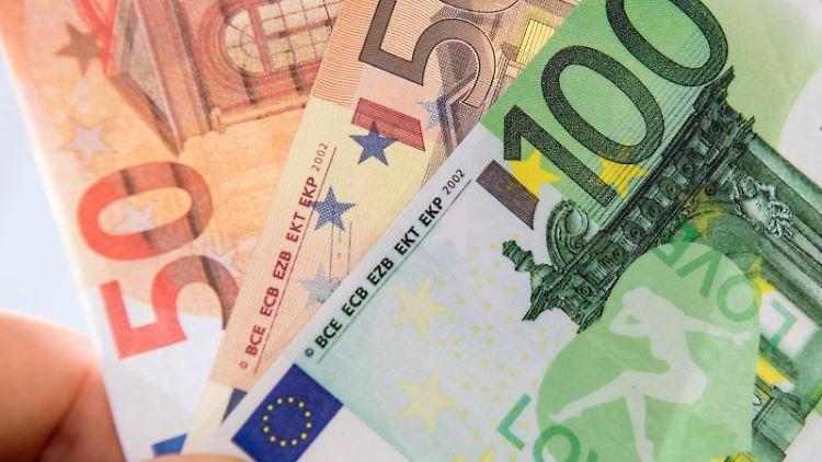 Ein Mann hält drei gefälschte Euro-Banknoten in der Hand. Foto: Fabian Sommer/Archivbild