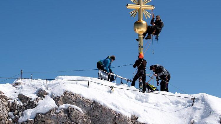 Schlosser bei Reparaturarbeiten am Gipfelkreuz auf der Zugspitze. Foto: Sven Hoppe