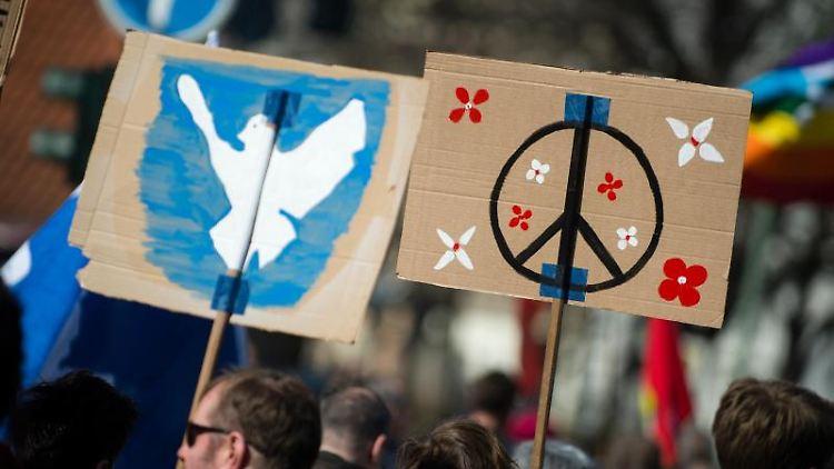 Demonstrierende tragen Schilder mit aufgemalten Friedenssymbolen und einer Friedenstaube. Foto: Gregor Fischer/Archivbild
