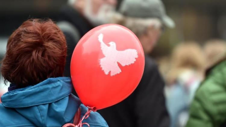Ein Luftballon mit einer Friedenstaube ist während eines Ostermarsches zu sehen. Foto: Caroline Seidel/Archivbild
