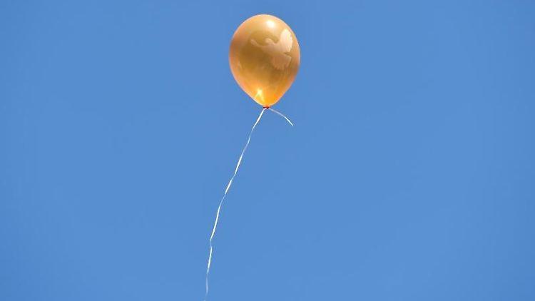 Ein Luftballon mit der Friedenstaube fliegt in den blauen Himmel. Foto: Caroline Seidel