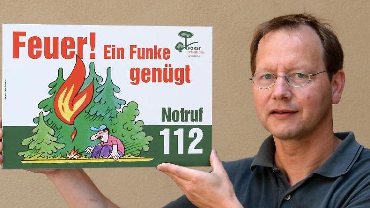 Der Waldbrandschutzbeauftragte von Brandenburg, Raimund Engel, zeigt eine Warntafel gegen Waldbrände. Foto: Ralf Hirschberger/Archivbild