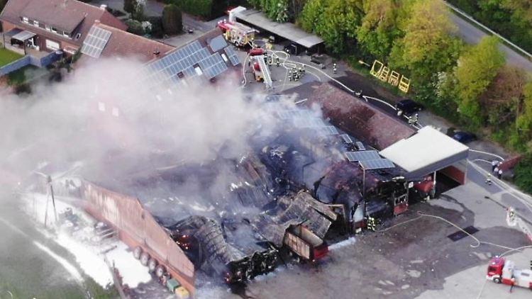 Feuerwehrautos stehen neben einer abgebrannten Lagerhalle. Foto: -/Nord-West-Media TV