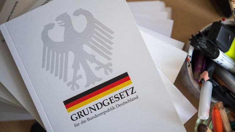 Eine Ausgabe des Grundgesetzes der Bundesrepublik Deutschland liegt in einer Schule neben Schreibutensilien. Foto: Monika Skolimowska/Archiv