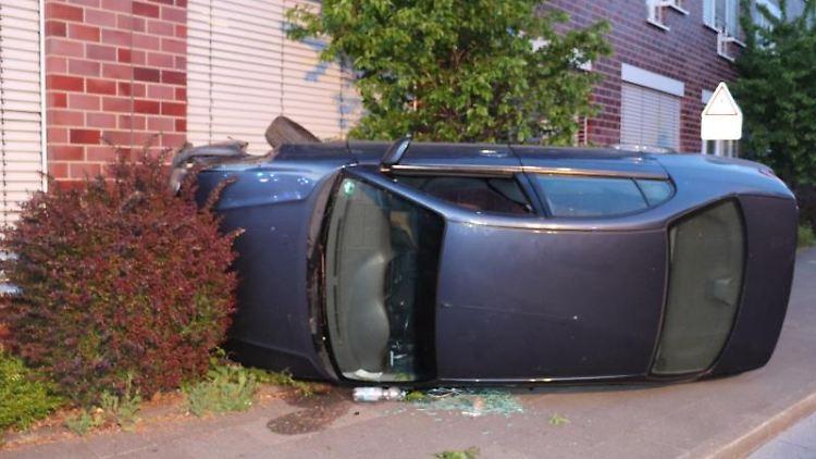 Ein Auto liegt an einer Hauswand auf der Seite. Foto: Polizei Mettmann