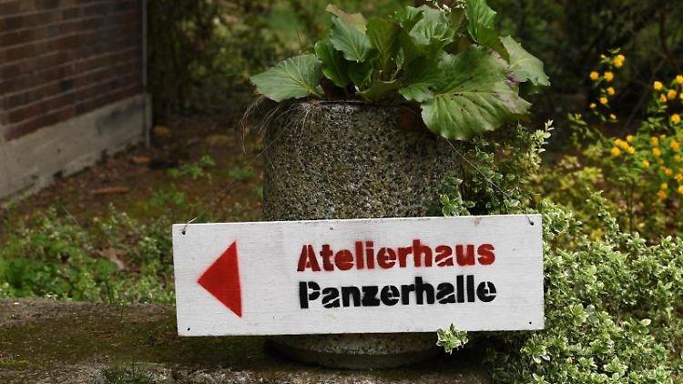 An einer Blumenschale haben Künstler ein Hinweisschild zum Atelierhaus