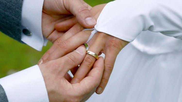 Ein Bräutigam streift bei der Trauung seiner Braut den Ehering über den Finger. Foto: Andreas Lander/Archivbild