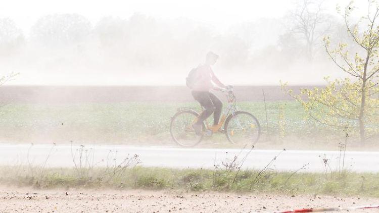 Eine Fahrradfahrerin fährt mit ihrem Rad über einen Fahrradweg, als starker Wind viel Sand von trockenen Feldern aufwirbelt. Foto:Julian Stratenschulte