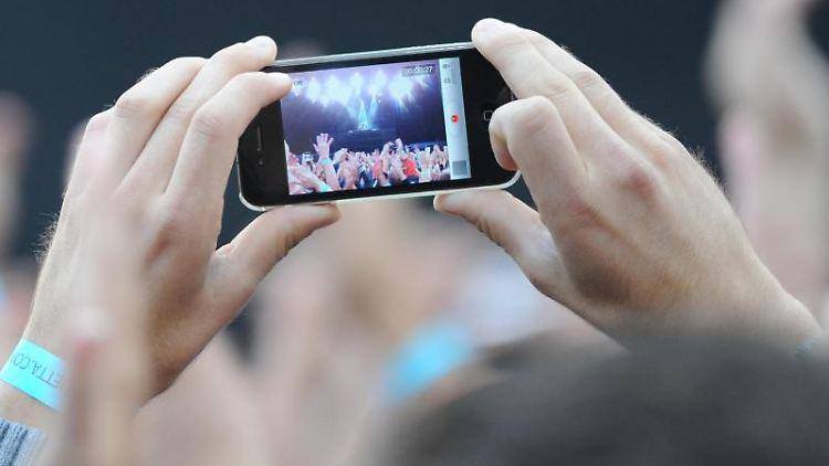 Ein Festivalbesucher filmt mit einem Handy den Auftritt eines Musikers. Foto: Marc Müller/Archivbild
