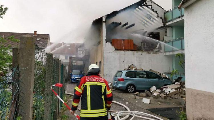 Ein Feuerwehrmann steht vor einem Haus, in dem eine Explosion einen Mann schwer verletzt hat. Foto: Julian Buchner/Einsatz-Report24