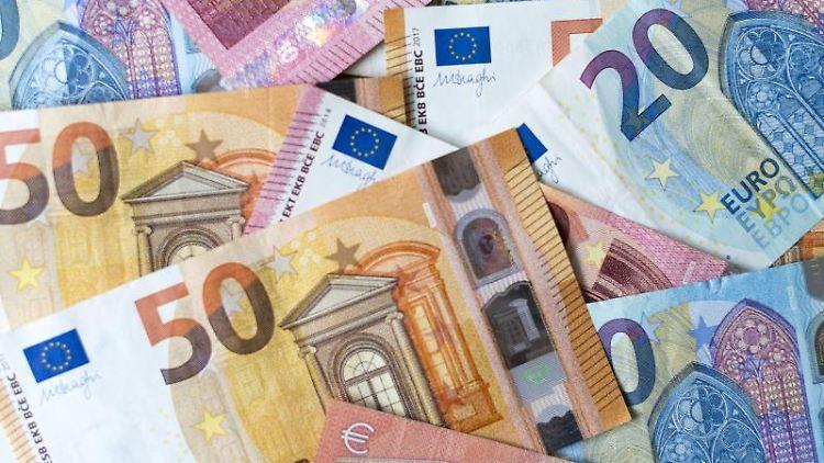 Zahlreiche Banknoten von 10, 20 und 50 Euro liegen auf einem Tisch. Foto: Monika Skolimowska/Archivbild