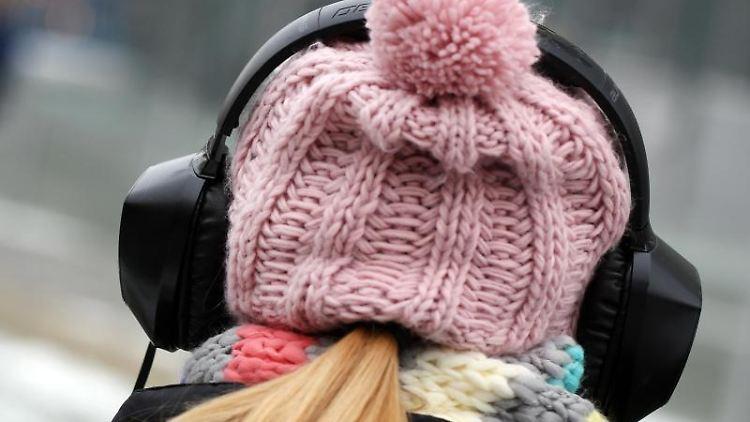Eine junge Frau hört über einen Kopfhörer Musik. Foto: Martin Gerten/Archivbild