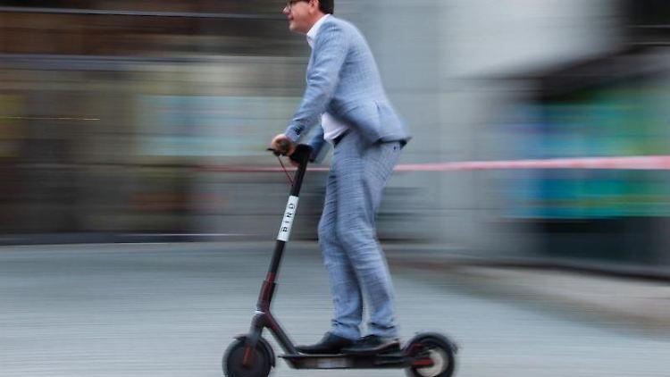 Ein Mann fährt mit einem E-Tretroller des US-amerikanischen E-Scooter-Sharing Anbieters