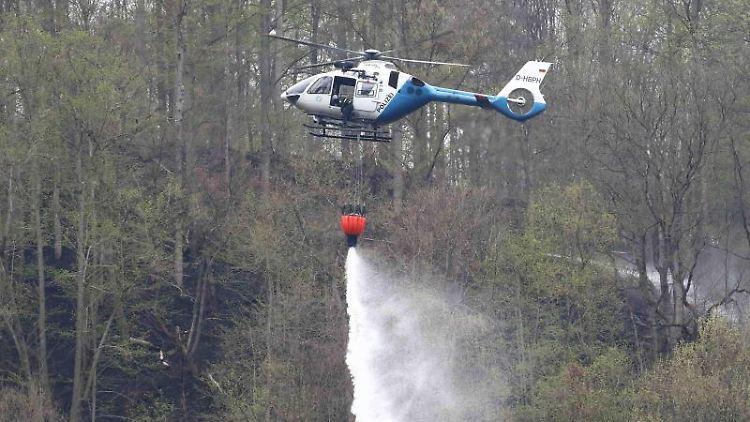 Ein Polizeihubschrauber löscht einen Brand im Wald an der Bleilochtalsperre. Foto: Bodo Schackow/Archivbild