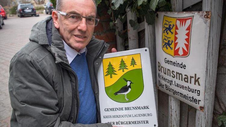 Iain Macnab, Bürgermeister der kleinen Gemeinde Brunsmark, hält das Bürgermeisterschild mit neuem Wappen hoch. Foto: Jens Büttner/Archivbild