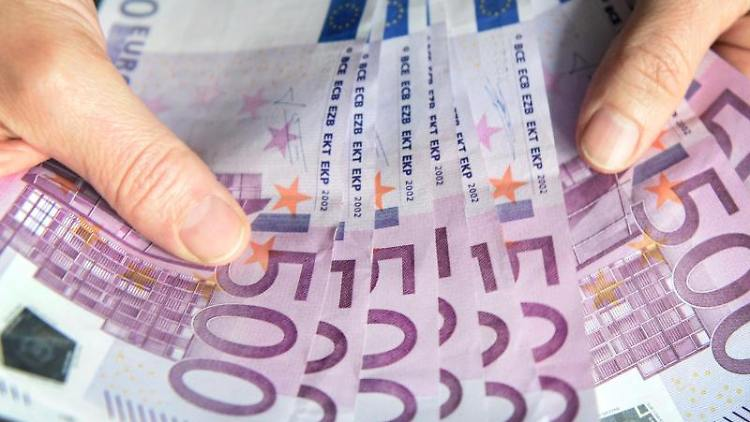 Eine Frau zählt 500-Euro-Geldscheine. Foto: Patrick Seeger/Archivbild