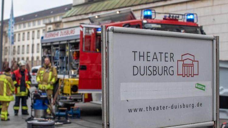Feuerwehrleute stehen vor dem Stadttheater. Foto: Christoph Reichwein/Archivbild