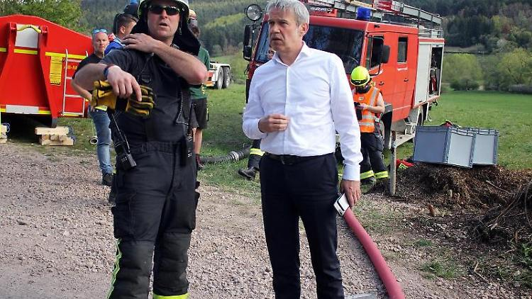 Georg Maier (SPD, r), Thüringer Innenminister, unterhält sich mit einem Feuerwehrmann. Foto: WichmannTV
