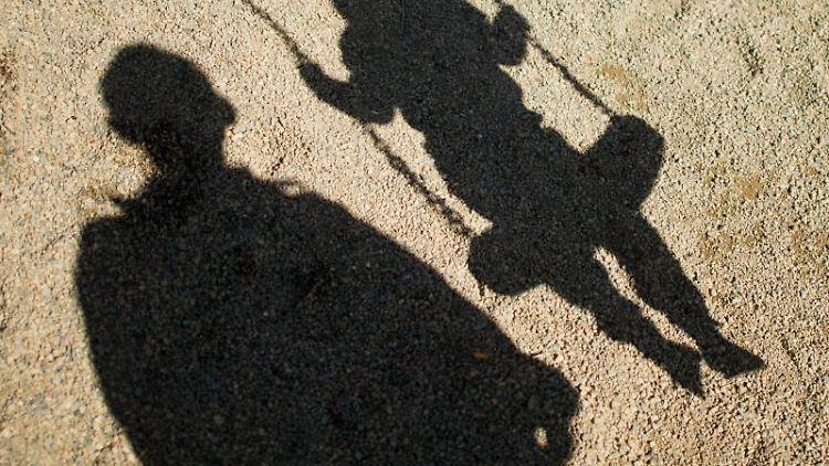 Der Schatten von einem Mann und einem Kind fallen auf Sand auf einem Spielplatz. Foto: Julian Stratenschulte/Archivbild