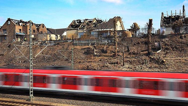 Ein Zug fährt in Siegburg an ausgebrannten Wohnhäusern vorbei. Foto: Oliver Berg/Archivbild