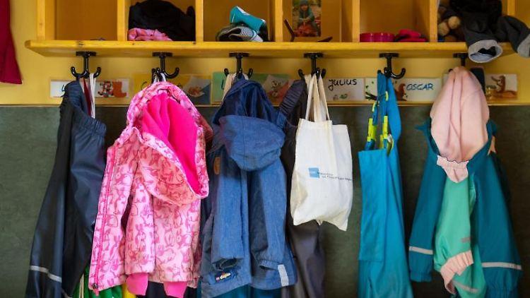 Jacken und Taschen hängen im Eingangsbereich in einem Kindergarten. Foto: Monika Skolimowska/Archivbild