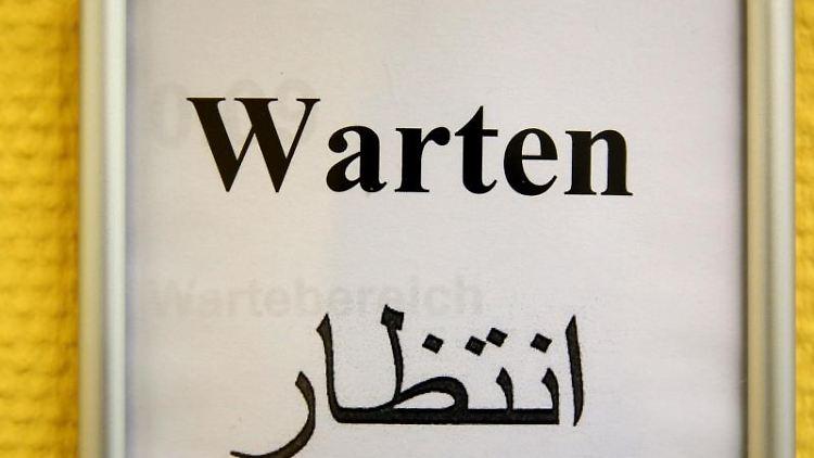 Ein Schild in deutscher und syrisch-arabischer Sprache weist auf ein Wartezimmer hin. Foto: Jan Woitas/Archivbild
