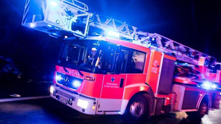 Ein Drehleiterwagen der Feuerwehr fährt mit Blaulicht über eine Straße. Foto: Marcel Kusch/Archiv