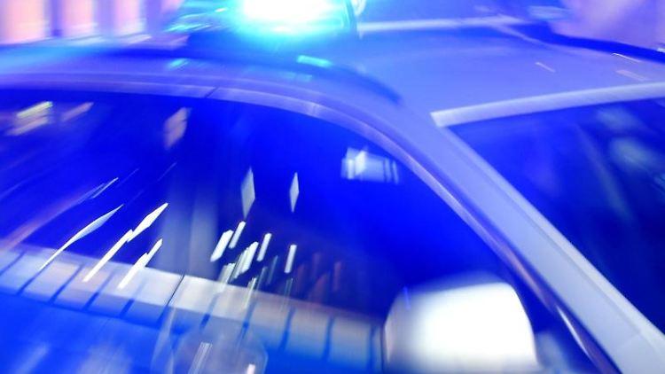 Ein Streifenwagen der Polizei fährt mit eingeschaltetem Blaulicht auf der Strasse. Foto: Carsten Rehder/Archivbild