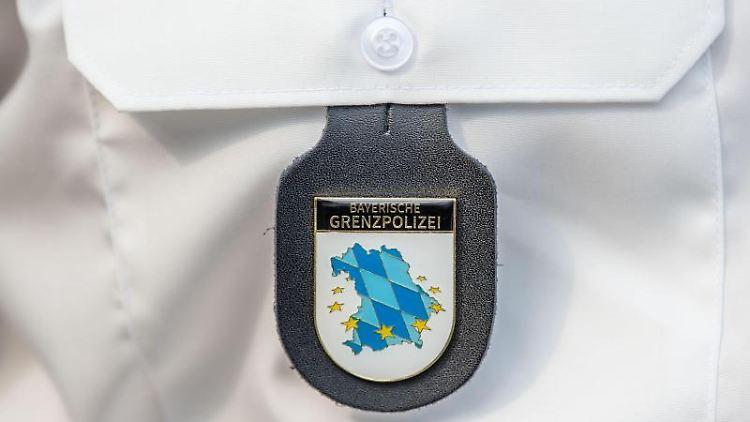 Das Emblem der bayerischen Grenzpolizei hängt am Hemd eines Polizeibeamten. Foto: Lino Mirgeler/Archivbild