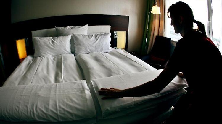 Ein Zimmermädchen macht in einem Hotel das Bett. Foto: Oliver Berg/Archivbild