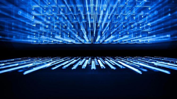 Die beleuchtete Tastatur eines Laptops spiegelt sich in einem Bildschirm. Foto: Silas Stein/Archiv