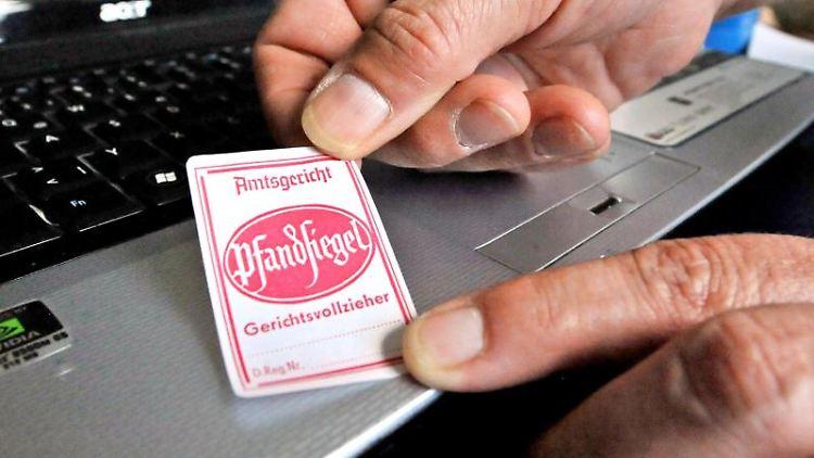 Ein Pfandsiegel wird auf einen Laptop geklebt. Foto: Georg-Stefan Russew/Archivbild