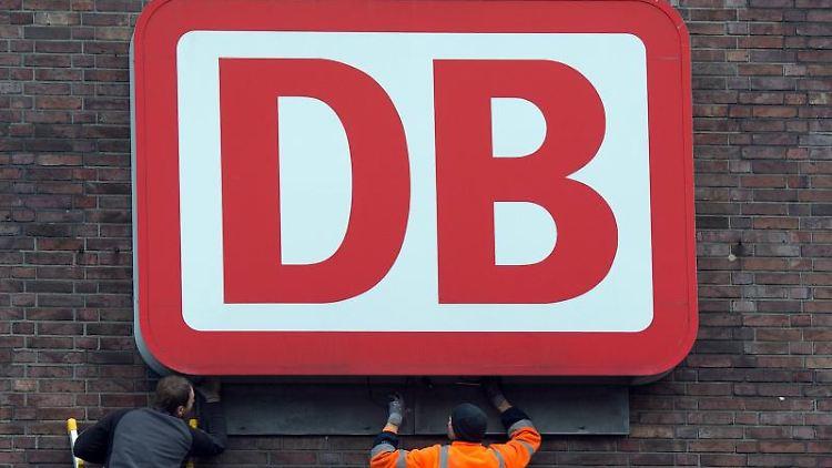 Monteure arbeiten an einem Unternehmensschild der Deutschen Bahn. Foto: Federico Gambarini/Archiv