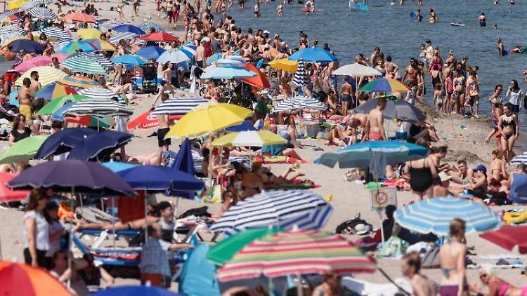 Zahlreiche Urlauber genießen Strand und Meer. Foto: Markus Scholz/Archivbild
