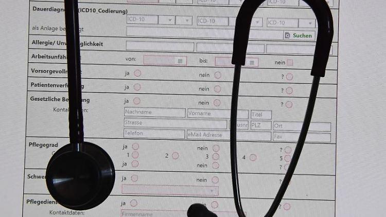 Ein Stethoskop hängt vor einer auf einem Bildschirm dargestellten digitalen Patientenakte. Foto: Stefan Sauer/Archiv
