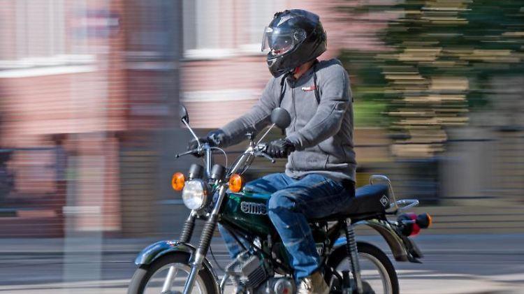 Ein Fahrlehrer fährt auf einem Simson S51 Moped durch die Stadt. Foto: Hendrik Schmidt/Archvbild