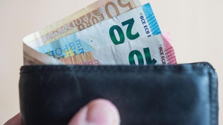 Geldscheine stecken in einem Geldbeutel. Foto: Lino Mirgeler/Archivbild