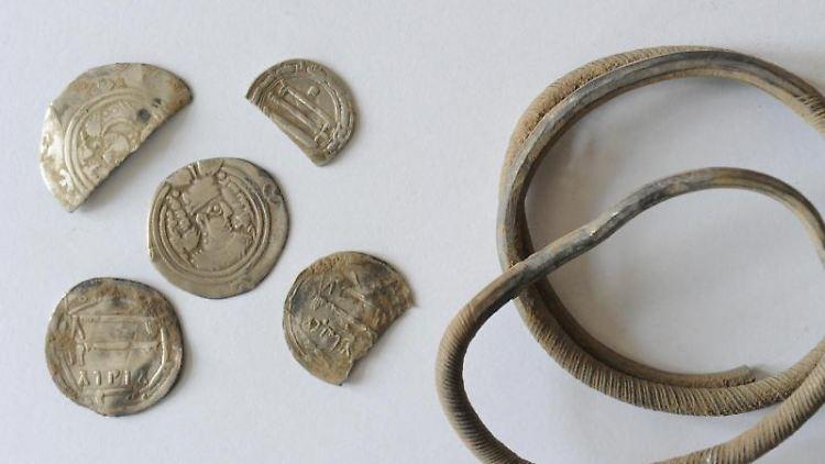 Blick auf einen Armreif und einzelne Münzen aus dem arabischen Raum. Die Exponate gehören zum Münzschatz von Anklam. Foto: Stefan Sauer/Archiv