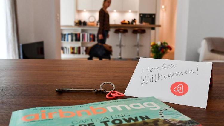 Ein Schlüssel mit einem Airbnb-Anhäger, ein Airbnbmag-Magazin und eine Herzlich-Willkommen-Karte liegen in der Wohnung eines Airbnb-Gastgebers). Foto: Jens Kalaene/Archivbild