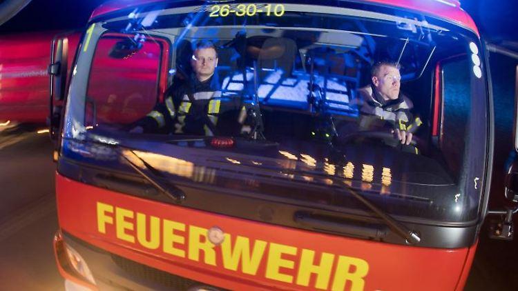Feuerwehrleute sitzen für Fotoaufnahmen in einem Leiterwagen (Aufnahme mit langer Verschlusszeit). Foto: Julian Stratenschulte/Archivbild