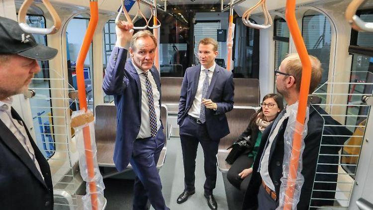Burkhard Jung (SPD, 2.v.l), und Samuel Kermelk (M.), Geschäftsführer der HeiterBlick GmbH, in einer Straßenbahn. Foto: Jan Woitas/Archivbild