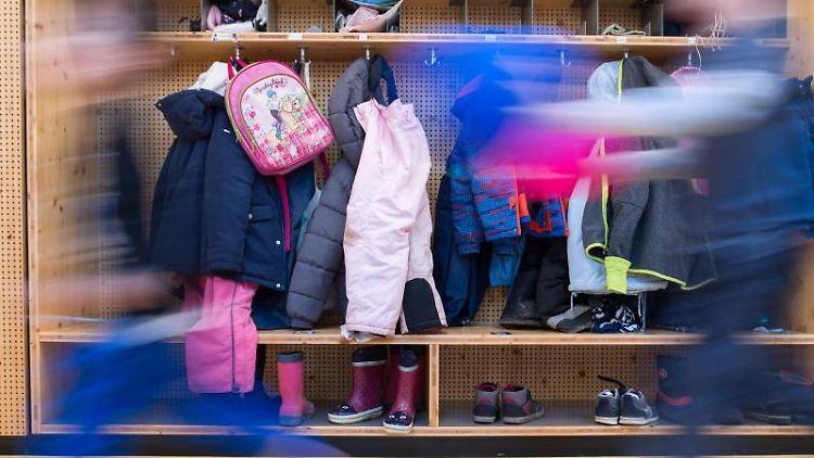 Zwei Kinder laufen vor einer Garderobe in einer Kindertagesstätte vorbei. Foto: Sebastian Gollnow/Archiv