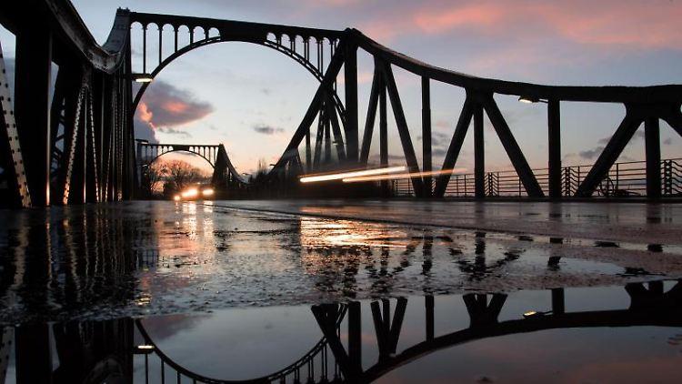 Teile der Glienicker Brücke spiegeln sich nach einem Regenschauer in einer Pfütze. Foto: Ralf Hirschberger/Archivbild