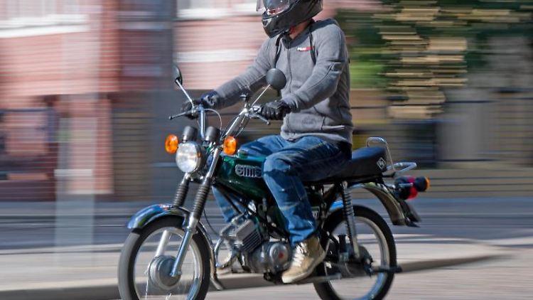 Ein Fahrlehrer auf einem Moped. Foto: Hendrik Schmidt/Archivbild