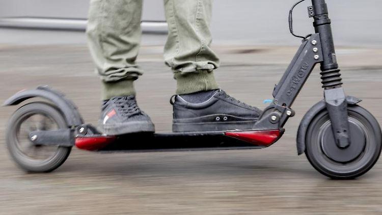 Ein Mann fährt mit einem E-Scooter auf einem Gehweg. Foto: Christoph Soeder/Archivbild