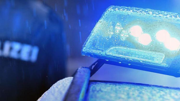 Ein Polizist steht im Regen vor einem Streifenwagen dessen Blaulicht aktiviert ist. Foto: Karl-Josef Hildenbrand/Archivbild