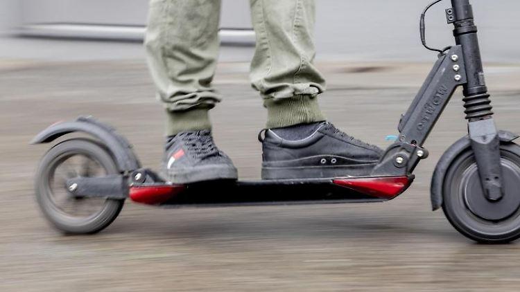 Ein Mann fährt mit einem E-Scooter auf einem Gehweg. Foto:Christoph Soeder/Archivbild