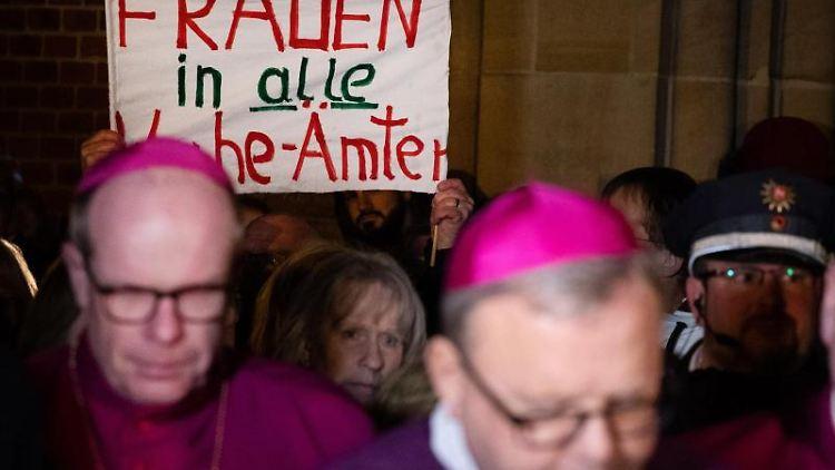 Frauen der kfd demonstrieren im niedersächsischen Lingen. Davor steht Franz-Josef Bode, Osnabrücker Bischof. Foto:Friso Gentsch/Archiv